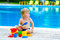 Toddler by the pool palying with toy bucket set
