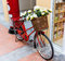 Red painted bicycle with a bucket of white flowers
