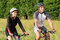 Young Couple Riding Bicycle In Meadow