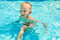 Little boy swims in pool