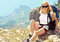Young Woman Traveler with backpack relaxing on Mountain summit rocky cliff with aerial view of Sea