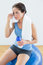 Tired woman with towel around neck and waterbottle on exercise ball