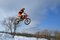 Motocross winter, high flying motorcycle racer over snowdrifts