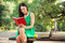 Beautiful young woman with toothy smile reading book in the park