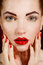 Close-up portrait of sexy european young woman model with glamour make-up and red bright manicure. christmas makeup, bloody red li