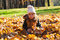 Little girl sits on fallen leaves