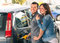 Happy couple at fuel station pumping gasoline at gas pump