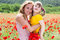 Mother playing with her child in poppy field