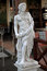 Classical stone sculpture of a young male musician with naked to