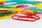 Multicolored office paperclips on white desktop closeup