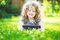 Charming little girl lying on the grass and holds in hands tablet