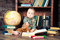 Cute baby boy sitting with globe, books and drawing pencils