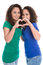 Happy young girls making heart with hands: real twin sisters.