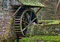 Moss covered water wheel and stone retaining wall of a historic