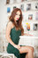 Fashionable attractive young woman in green dress sitting in restaurant. Beautiful redhead posing in elegant scenery with juice