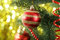 Christmas baubles on christmas tree on lights background, close up