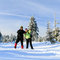 Happy couple hiking on snow trail in winter mountains