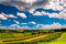 Beautiful summer clouds over rolling hills and farm fields in ru