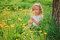 Cute child girl on dandelion flower field