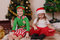 Children in Christmas costumes opening presents