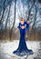 Back side view of lady in long blue dress posing in winter scenery, royal look. Fashionable blonde woman with forest in background