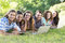 Smiling friends in the park using tablet pc and laptop