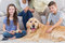 Siblings with dog and parents sitting behind