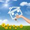 Hand holding house icon and key. Background of sky