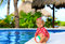 Cute toddler girl playing with ball in swimming