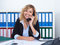 Blond businesswoman at office speaking with client at phone