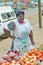 Black Zulu woman with tribal makeup on her face sells vegetables in Zulu village in Zululand, South Africa