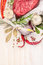 Raw meat with herbs and spices: bay leaf, garlic, pepper on white wooden background, top view, close up