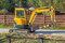 Small yellow crawler excavator for screwing piles