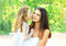 Loving daughter kissing mother, happy young mom and child in warm sunny summer day on the nature