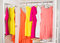 Row of bright colorful dress hanging on coat hanger, shoes and h