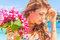 Young happy girl with flower bouquet on tropical sea and beach