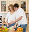 Pregnant woman and her husband in kitchen cook food