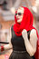 Elegant blonde woman in red scarf and sunglasses posing on stree