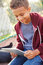 Young Boy Using Digital Tablet Sitting In Park