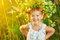 Funny happy baby child girl in a wreath on nature laughing in su
