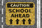 Road with School ahead caution sign