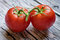 Close-up view of a pair of red tomatoes on wood table