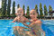Little baby boy swimming in outdoor pool with mother