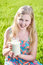 Girl with long hair holds jug of milk in sunny meadow