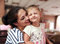 Happy mother and cute enjoying girl cuddling with love indoor