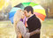 Portrait of young loving couple with colorful umbrella hugging autumn