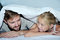 Smiling father and his daughter having fun lying on a bed