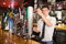 Bartender holding glass standing in front of beer dispenser