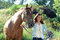 A teen girl walks with her horse