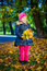 Cheerful little girl with bouquet of maple leaves in autumn park